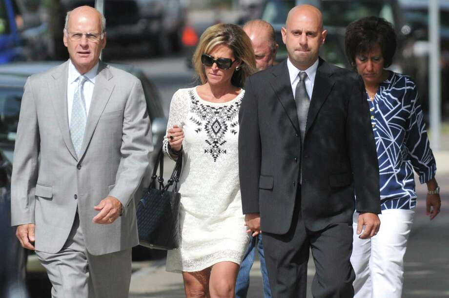Troy police officer Brian Gross, right, is escorted into Troy City Court by his wife, center, and attorney Stephen Coffey, left, Wednesday, July, 30, 2014, in Troy N.Y. Officer Gross has been charged with felony evidence tampering and other charges for allegedly tipping off a suspect about an impending raid by a State Police narcotics squad. (Cindy Schultz/Times Union)