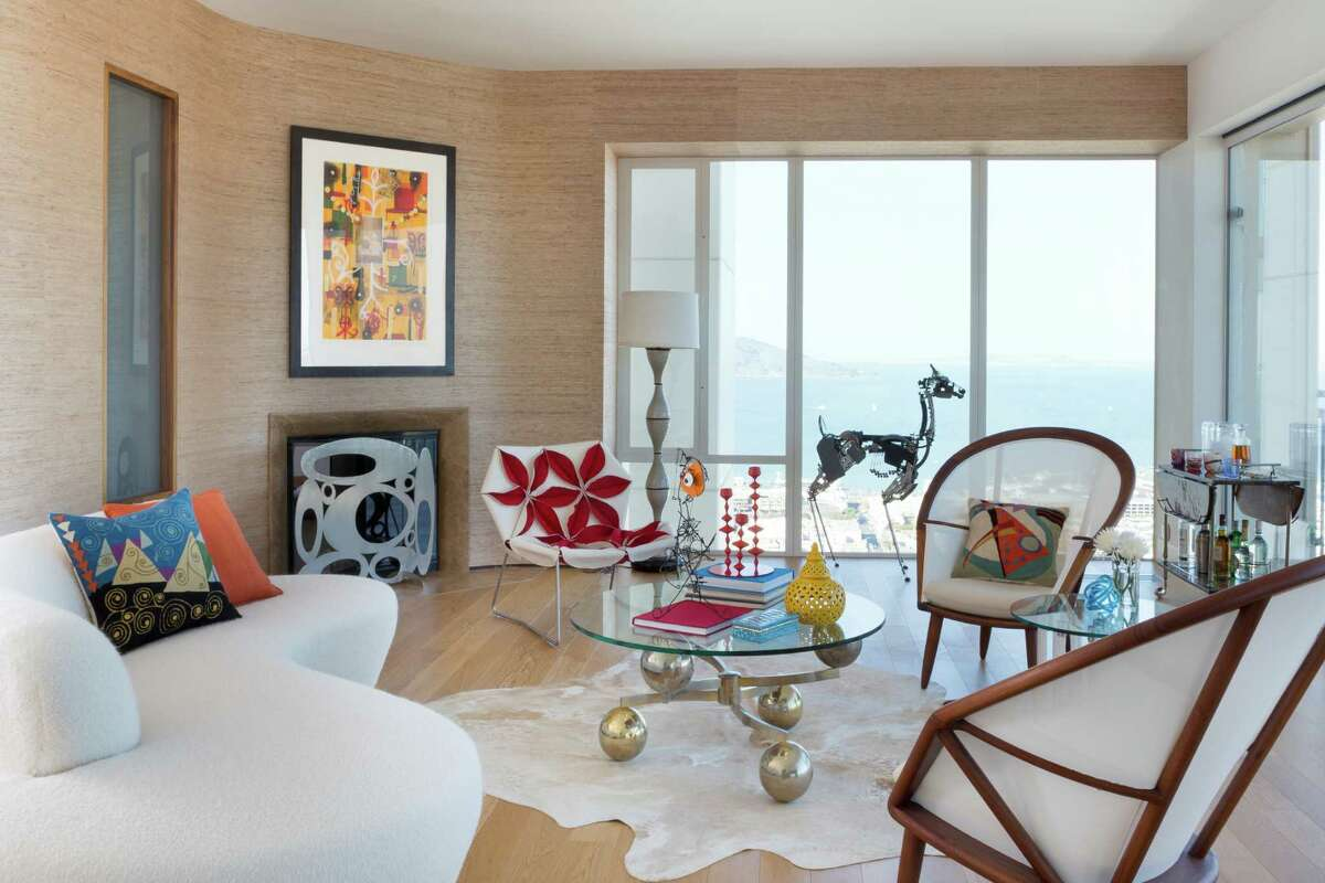 In the living room, a '70s-era Vladimir Kagan couch, Philip Nimmo fireplace screen, Patricia Urquiola's red-and-white Antibodi chair, Jeremy Mayer's
