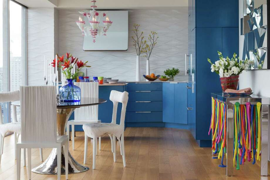"In the kitchen, Alex Angi's ""Rain of Colours"" console features multi-hued plastic extrusions. The vibrant table picks up on nearby colors, such as the blue kitchen cabinets and the pink Murano glass chandelier. Belgian artist Peter Traag's Mummy chairs and the Campana Brothers' Jenette chairs — both in white — surround the oval dining table and provide further textural interest. Photo: David Duncan Livingston / ONLINE_CHECK"