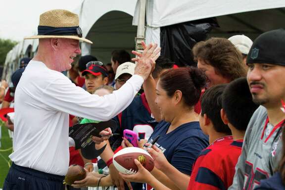 Houston Texans owner Bob McNair high fives a fan as he signs autographs during Texans training camp at the Methodist Training Center Wednesday, July 30, 2014, in Houston.