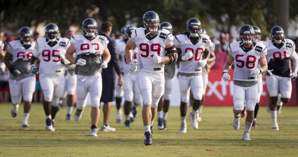 Texans defensive end J.J. Watt (99) leads the way as the Texans' defensive players run upfield durin