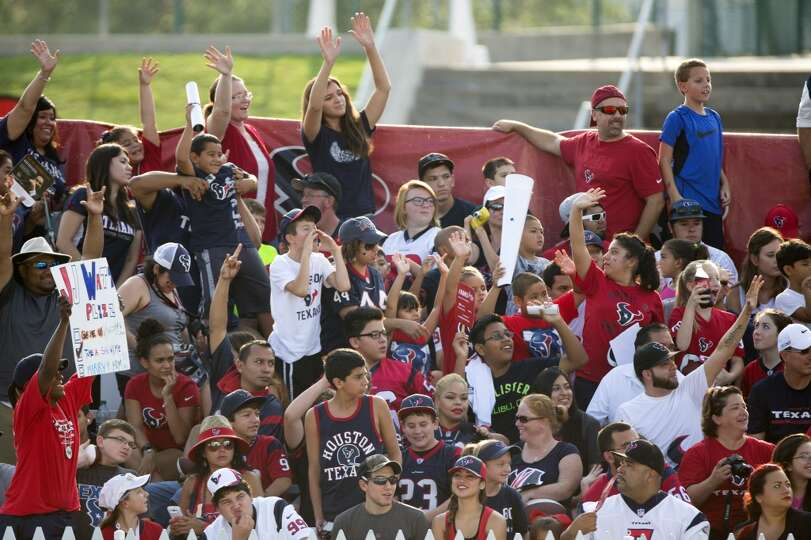 Texans fans cheer as they watch practice.