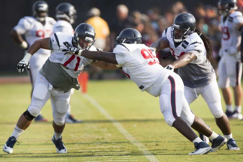 Texans nose tackle Austin Brown (71) runs a drill with nose tackle Jerrell Powe (95) and defensive t