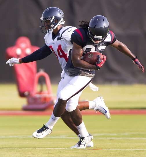 Texans wide receiver Keshawn Martin (82) is hit by cornerback A.J. Bouye (34) after making a catch.