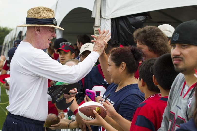 Houston Texans owner Bob McNair high fives a fan as he signs autographs during Texans training camp