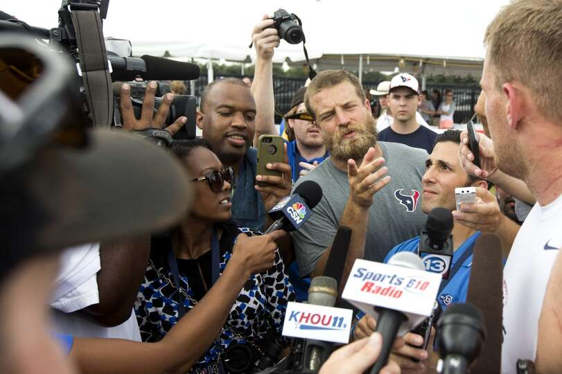 Houston Texans quarterback Ryan Fitzpatrick asks defensive end J.J. Watt, right, a question as Watt