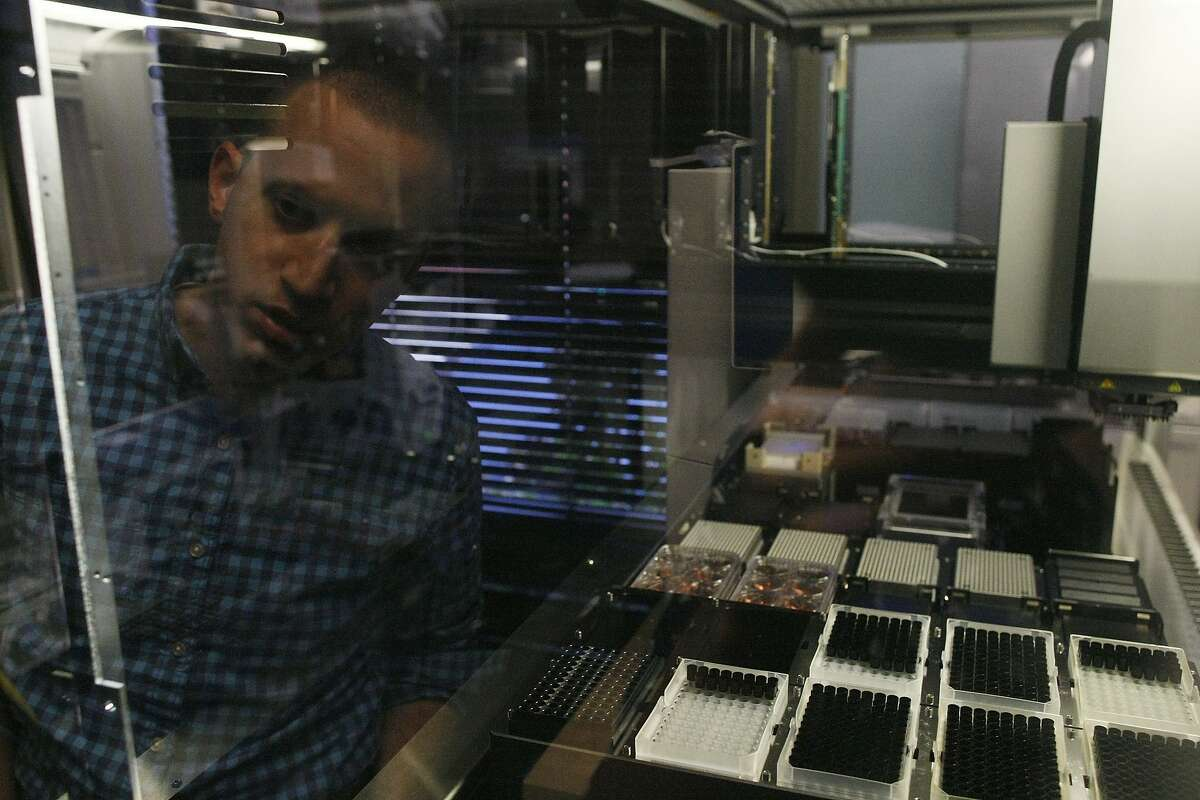 DJ Kleinbaum, co-founder of Emerald Cloud Labs, looks at a liquid handler on Tuesday, July 29, 2014 in Menlo Park, Calif. Companies such as Emerald Cloud Labs offer others to use their machinery to do experiments.