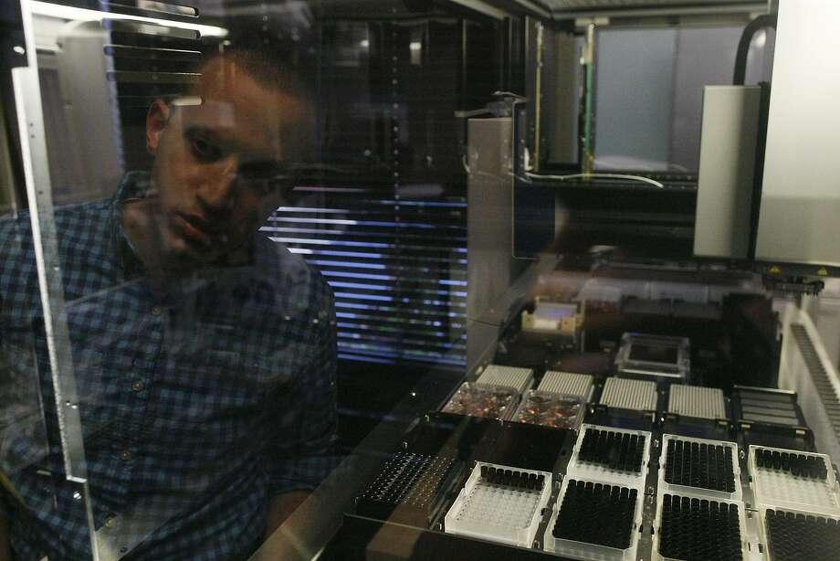 D.J. Kleinbaum, co-founder of Emerald Cloud Lab, observes a liquid handler, a machine that performs experiments. Photo: James Tensuan, The Chronicle