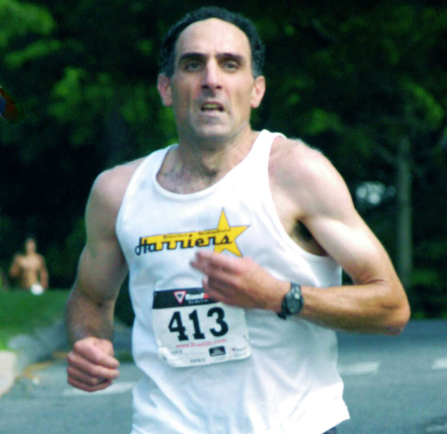 Multi-time champion Michael Nahom, 46, of New Milford crests Canterbury Hill en route to distinguishing himself with a sixth-place finish in Saturday's 47th annual New Milford 8-mile road race. Nearly three decades older than his chief hometown rivals, Nahom captured prestigous laurels as the first New Milflord finisher. July 26, 2014 Photo: Norm Cummings / The News-Times