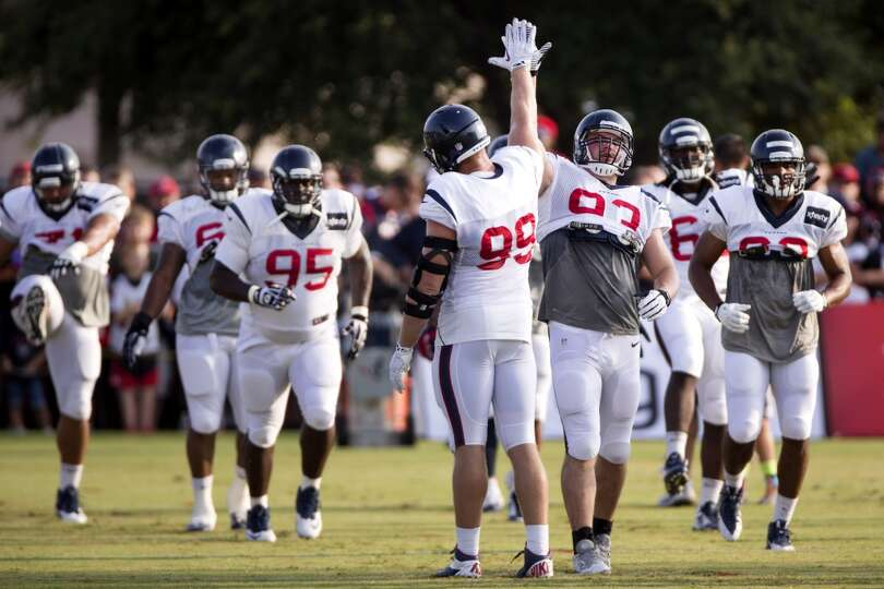 Texans defensive end J.J. Watt (99) high fives defensive end Jared Crick (93).