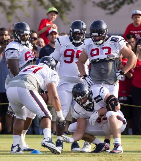 Texans nose tackle Austin Brown (71) reaches down to slap hands with defensive end J.J. Watt (99).