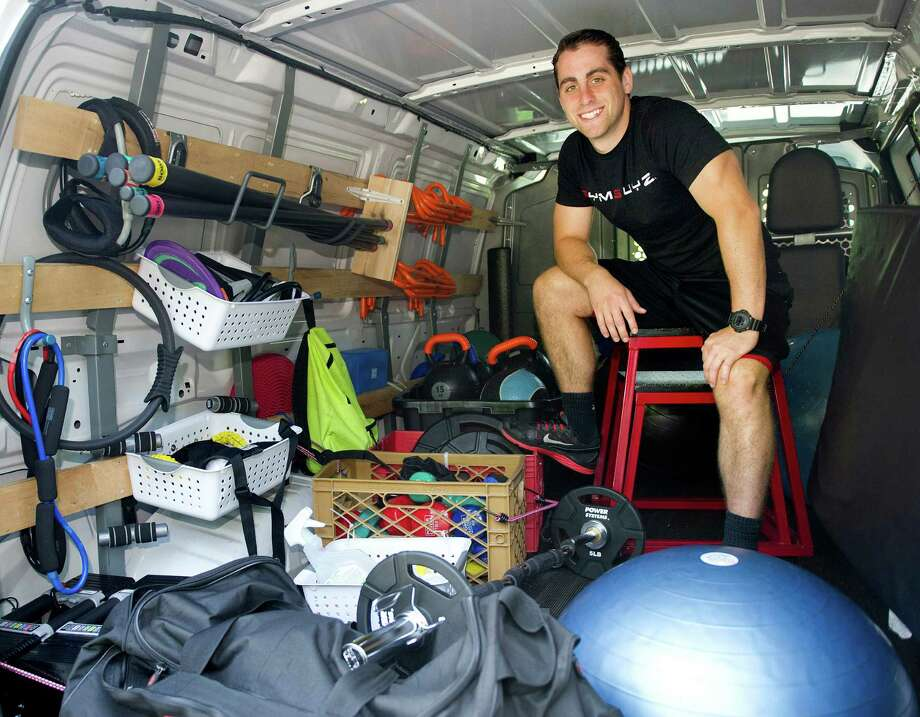 Sam Langer, owner of GYMGUYZ, poses for a photo with his van, which he uses to bring exercise equipment to clients, at Greens of Greenwich on Wednesday, July 30, 2014. Photo: Lindsay Perry / Stamford Advocate
