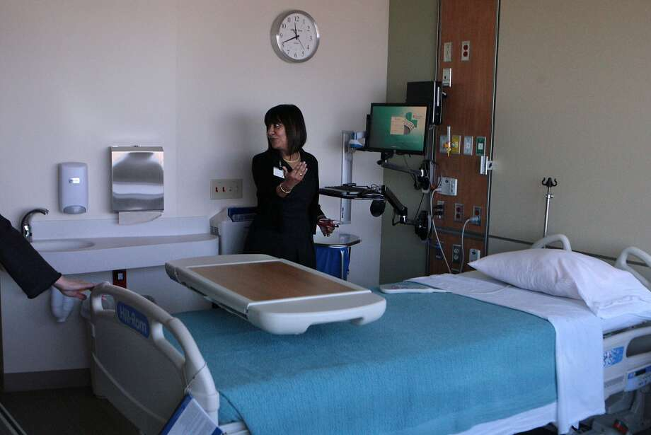 Julie Petrini, chief operating officer at Alta Bates Summit Medical Center, tours a private hospital room at Merritt Pavilion, the hospital's new 238-bed facility in Oakland. The hospital opens Sunday. Photo: Kevin N. Hume, The Chronicle