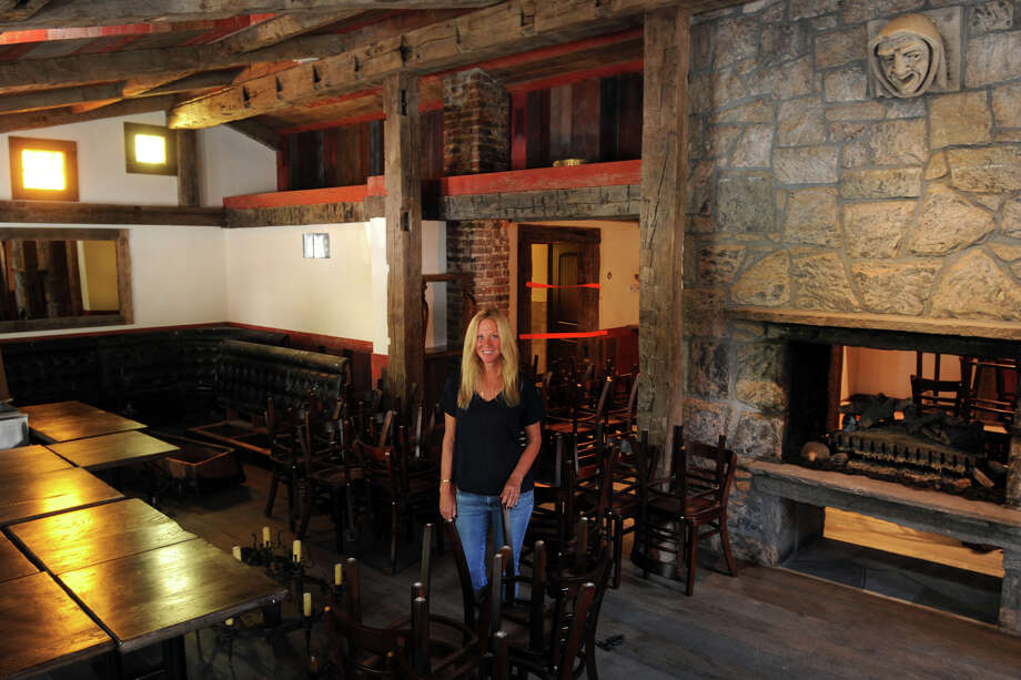 Daneen Grabe stands in what will be the main dining room at the Little Pub, which will soon open in Greenwich, Conn. Photo: Ned Gerard / Connecticut Post