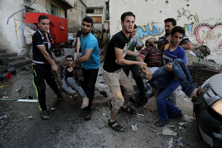 Palestinians help carry injured men following an Israeli air strike in the eastern Gaza City neighborhood of Shijaiyah. Fighting between Israel and Hamas continues to escalate in the embattled coastal territory. Photo: Adel Hana, Associated Press