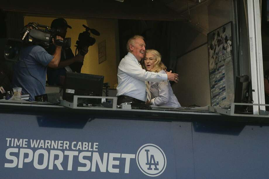 Vin Scully and his wife Sandi hug in the Dodgers' broadcast booth during Tuesday night's game. Photo: Jae C. Hong, Associated Press