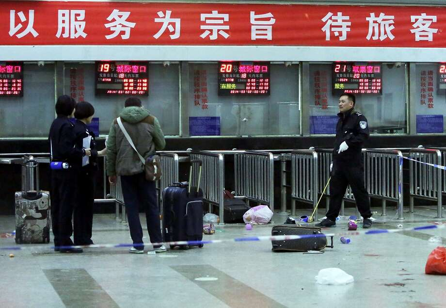 "(FILES) This file photo taken on March 2, 2014 shows Chinese police investigators inspecting the scene of an attack at the railway station in Kunming, in southwest China's Yunnan province.  A clash in Xinjiang, home to China's mostly Muslim Uighur minority, left nearly 100 people dead or wounded, an exile group said on July 30, 2014 after what authorities called a ""terror attack"" on a police station and township. Beijing commonly blames separatists from Xinjiang for carrying out terror attacks which have grown in scale over the past year and spread outside the restive and resource-rich region.  Among the most shocking incidents were a market attack in Xinjiang's capital Urumqi in May in which 39 people were killed, and a deadly rampage by knife-wielding assailants at a train station at Kunming in China's southwest in March, which left 29 dead.      CHINA OUT     AFP PHOTO / FILESSTR/AFP/Getty Images Photo: Str, AFP/Getty Images"