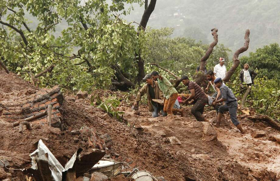 Rescue workers carry the body of a victim in Malin village in the western Indian state of Maharashtra. Landslides swept away scores of houses there. Photo: Associated Press