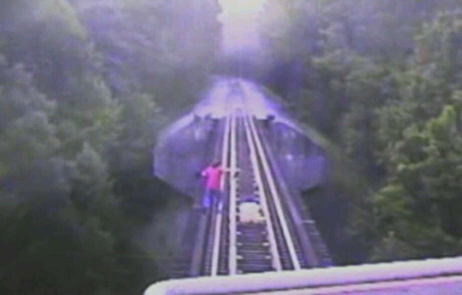 In this frame grab from surveillance video, two women scramble down the track ahead of a freight train coming toward them on an 80-foot-high trestle in Indiana. The women survived, apparently unhurt, but train personnel recorded their car's license plate as they drove away, and officials say they may press charges. Photo: HONS / Indiana Rail Road via WRTV