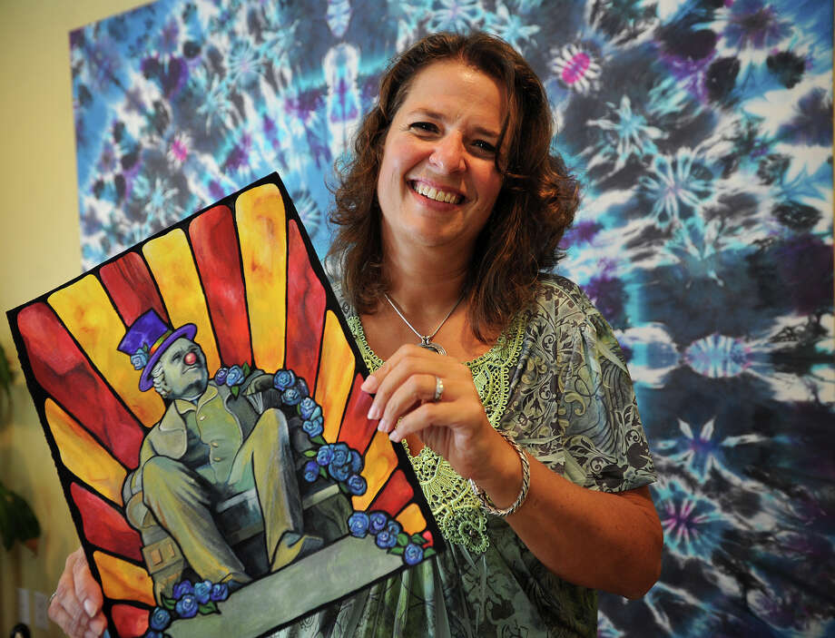 Artist Laura Dowling, of Monroe, holds her original painting which won the poster design contest for the 2014 Gathering of the Vibes Music Festival being held this week at Seaside Park in Bridgeport. The poster features the park's statue of P.T. Barnum, decked out in a top hat and clown nose. Photo: Brian A. Pounds / Connecticut Post