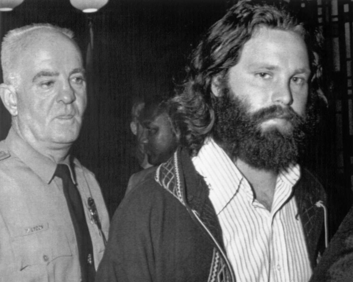 Jim Morrison, the unhappiest tourist in Miami. Singer Jim Morrison leaves the courtroom in Miami, Florida on Oct. 30, 1970, in the custody of a police officer after he was sentenced to six months in jail and fined for $500 for using profanity in public and indecent exposure. Morrison remained free on a $50,000 bond pending disposition of an appeal. The charges stemmed from a 1969 performance by Morrison in an appearance in Miami Florida, USA with The Doors. (AP Photo)