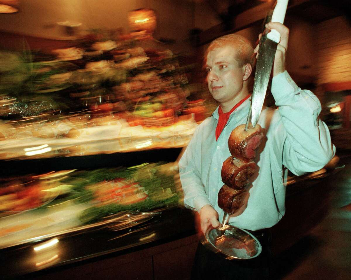 Gaucho Jarbas Gottardo carries a skewer of meat while serving guests at Fogo de Chao on Westheimer.