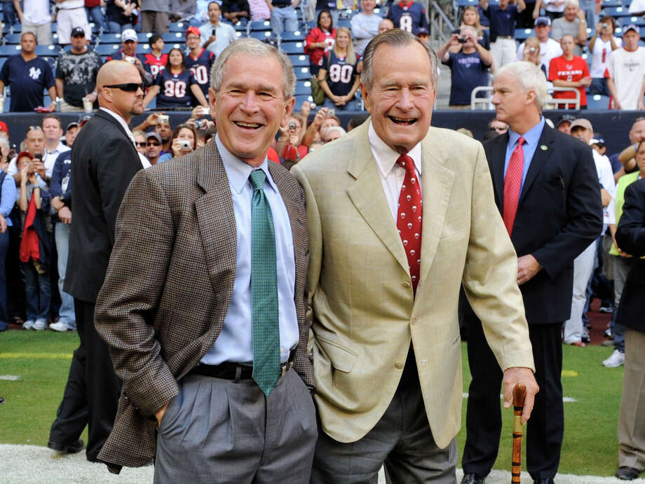 "FILE - This Oct. 25, 2009 file photo shows former Presidents George H. W. Bush, right, and George W. Bush before the Houston Texans NFL football game against the San Francisco 49ers in Houston. George H. W. Bush and George W. Bush are cooperating with a historian for a joint biography about the former presidents. ""Presidents Bush: A Portrait of a Father and Son,"" by Mark K. Updegrove, has been acquired by Henry Holt and Company. The book is scheduled for Spring 2016. (AP Photo/Dave Einsel, File) Photo: Dave Einsel, FRE / FR43584 AP"