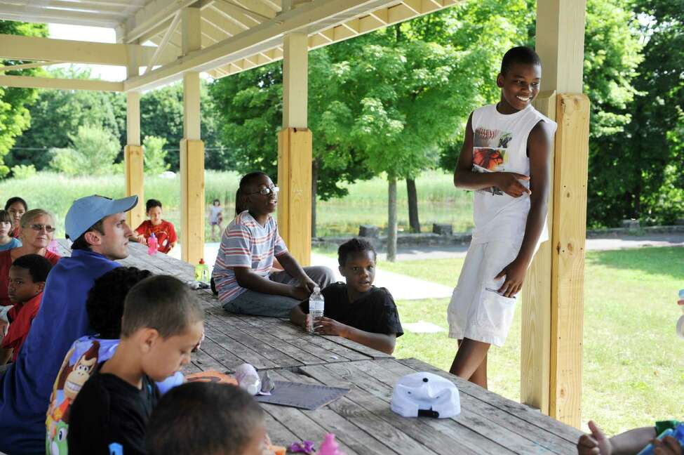 Esean Josephs, far right, 12, stands up to try his hand a rapping during discovery time at the Steinmetz Park Summer Camp Wednesday, July 30, 2014, in Schenectady, N.Y. The camp, in its first year, is put on by the Schenectady Inner City Ministry. The four-week program is free for the children and this years camp served 24 children. Along with this camp, the ministry operates Camp Fowler and also runs a summertime lunch program in the city feeding roughly 1,900 children daily. (Paul Buckowski / Times Union)