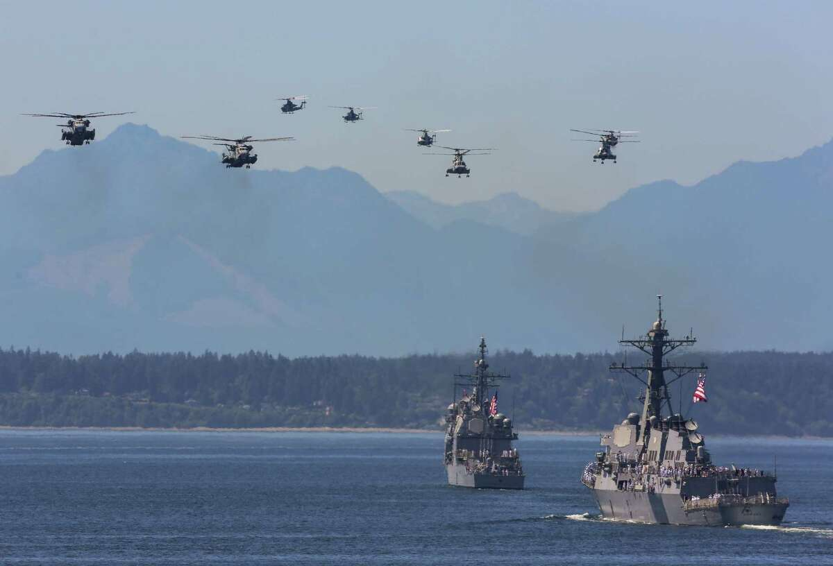 Military aircraft perform a flyover during the Seafair Parade of Ships & Flight. Hundreds of spectators lined up along Elliott Bay to watch the incoming ships and military flyovers on July 30, 2014.