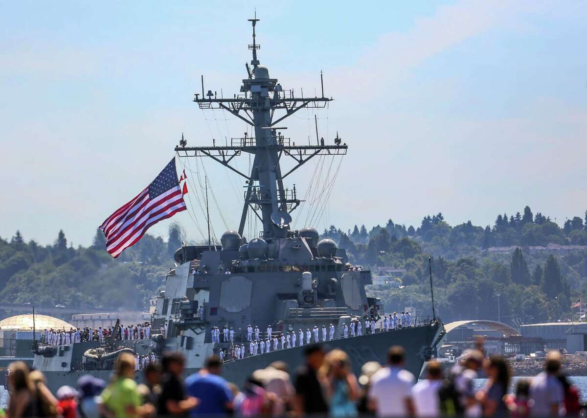 Spectators watch the USS Howard pass during the Seafair Parade of Ships & Flight. Hundreds of spectators lined up along Elliott Bay to watch the incoming ships and military flyovers on July 30, 2014.