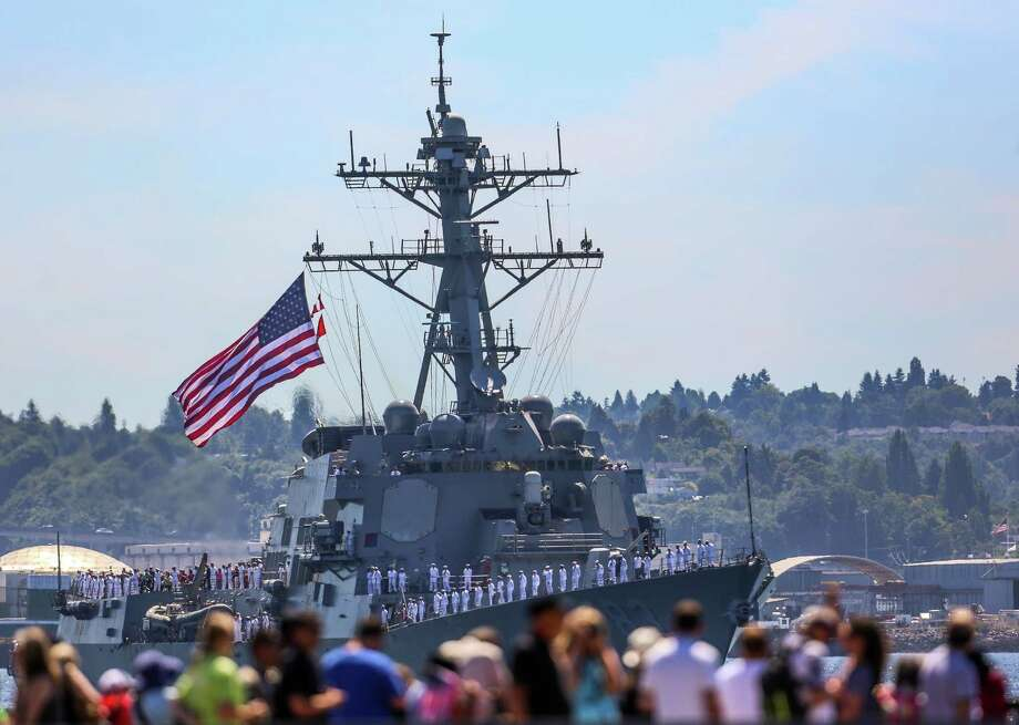 Spectators watch the USS Howard pass during the Seafair Parade of Ships & Flight. Hundreds of spectators lined up along Elliott Bay to watch the incoming ships and military flyovers on July 30, 2014. Photo: JOSHUA BESSEX, SEATTLEPI.COM / SEATTLEPI.COM