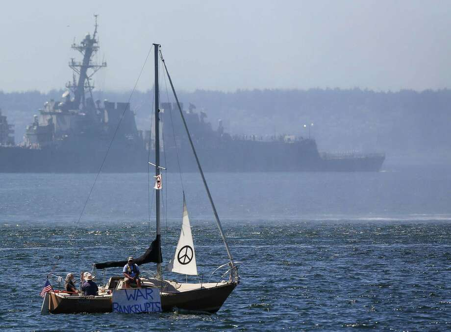 Protesters on a sail boat hold signs toward shore. Hundreds of spectators lined up along Elliott Bay to watch the incoming ships and military flyovers during the Seafair Parade of Ships & Flight on July 30, 2014. Photo: JOSHUA BESSEX, SEATTLEPI.COM / SEATTLEPI.COM