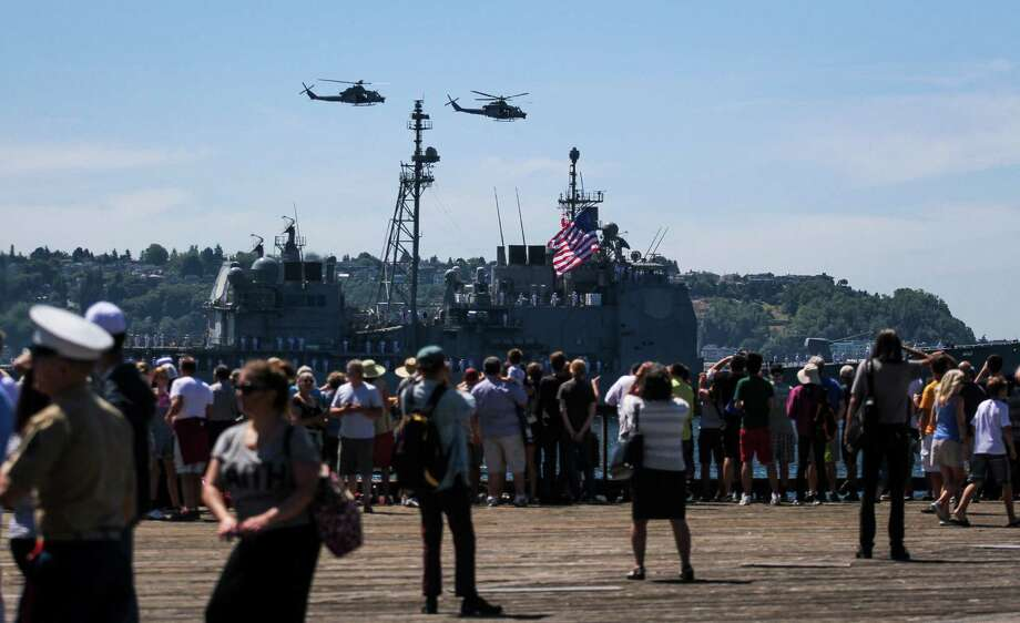 Spectators watch the USS Chancellorsville pass during the Seafair Parade of Ships & Flight. Hundreds of spectators lined up along Elliott Bay to watch the incoming ships and military flyovers on July 30, 2014. Photo: JOSHUA BESSEX, SEATTLEPI.COM / SEATTLEPI.COM
