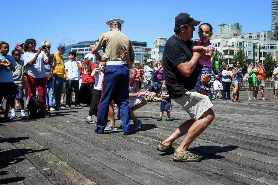 People dance along to the Marine Band songs during the Seafair Parade of Ships & Flight. Hundreds of spectators lined up along Elliott Bay to watch the incoming ships and military flyovers on July 30, 2014. Photo: JOSHUA BESSEX, SEATTLEPI.COM / SEATTLEPI.COM