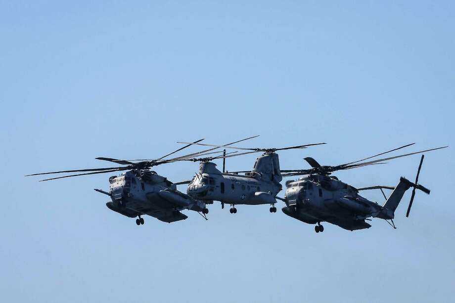 A CH-46 Sea Knight (center) and two AH-1Z Vipers perform a flyover during the Seafair Parade of Ships & Flight. Hundreds of spectators lined up along Elliott Bay to watch the incoming ships and military flyovers on July 30, 2014. Photo: JOSHUA BESSEX, SEATTLEPI.COM / SEATTLEPI.COM
