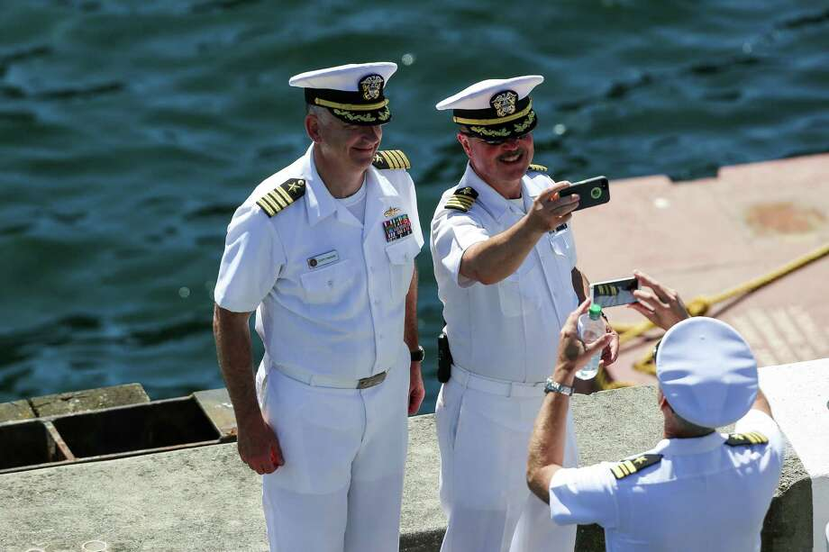 Men take a selfie while the USS Howard prepares to dock following the Seafair Parade of Ships & Flight. Hundreds of spectators lined up along Elliott Bay to watch the incoming ships and military flyovers on July 30, 2014. Photo: JOSHUA BESSEX, SEATTLEPI.COM / SEATTLEPI.COM
