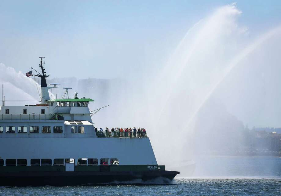 Ferry passengers get a close look at the The Leschi Seattle Fireboat. Hundreds of spectators lined up along Elliott Bay to watch the incoming ships and military flyovers during the Seafair Parade of Ships & Flight on July 30, 2014. Photo: JOSHUA BESSEX, SEATTLEPI.COM / SEATTLEPI.COM