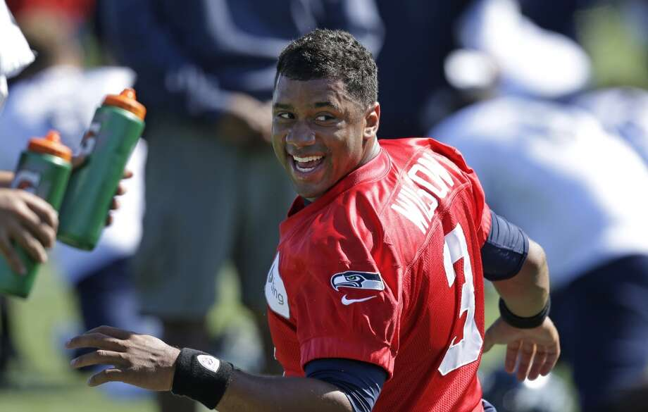 Seahawks quarterback Russell Wilson stretches at Seahawks training camp on Saturday, July 26, 2014. Photo: Elaine Thompson, Associated Press