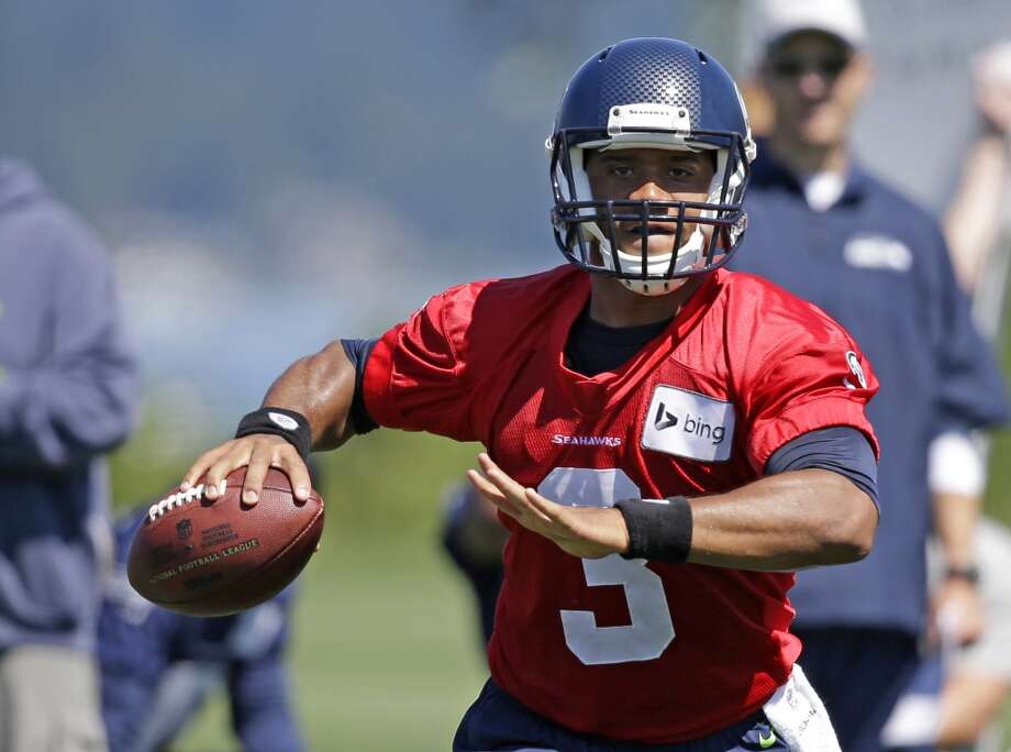 Wilson looks for a receiver at Seahawks training camp practice on Saturday, July 26, 2014. Photo: Elaine Thompson, Associated Press