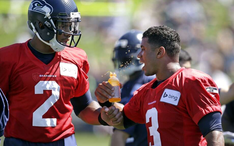 Qarterback Terrelle Pryor (2) teases fellow quarterback Russell Wilson by bumping his drink while walking past him at Seahawks training camp on Saturday, July 26, 2014. Photo: Elaine Thompson, Associated Press