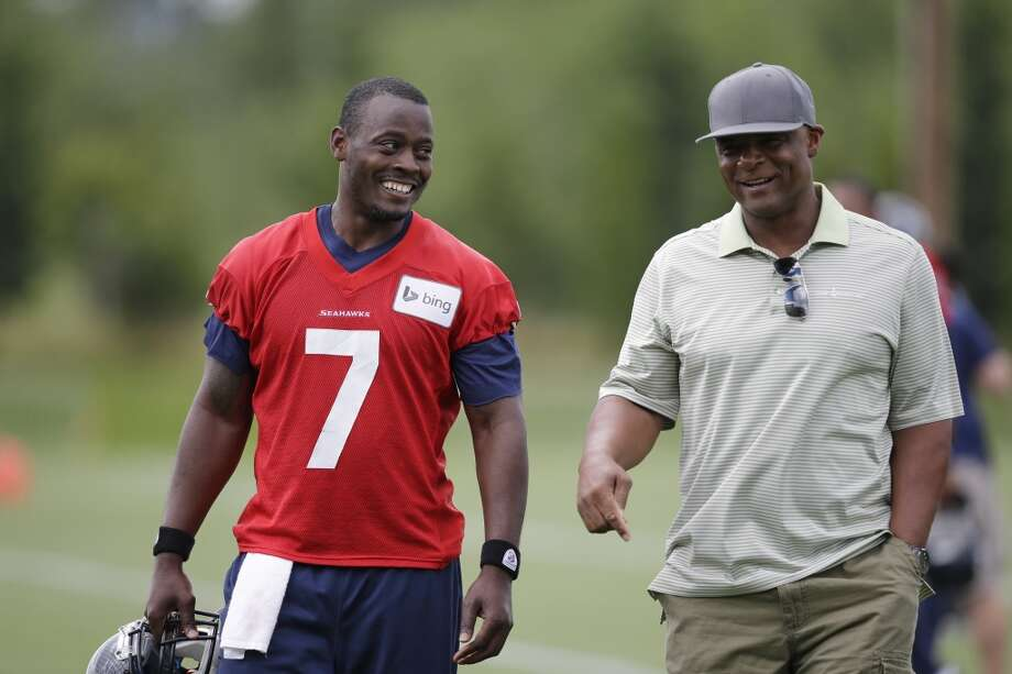 Tarvaris Jackson (7) walks off the field with former NFL quarterback Warren Moon after practice at Seahawks training camp on Friday, July 25, 2014. Photo: Associated Press