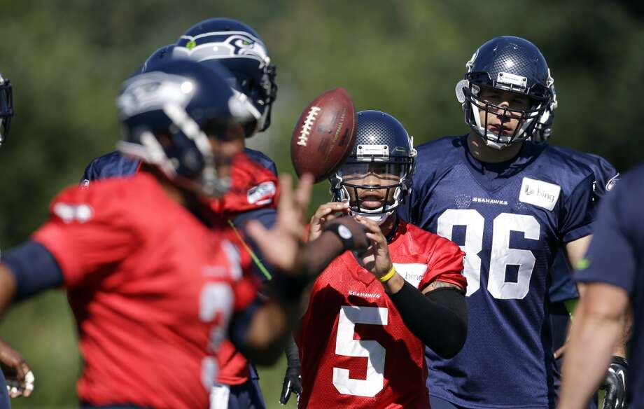 Seahawks quarterback B.J. Daniels (5) reaches for the ball during a drill at Seahawks training camp on Saturday, July 26, 2014. Photo: Elaine Thompson, Associated Press
