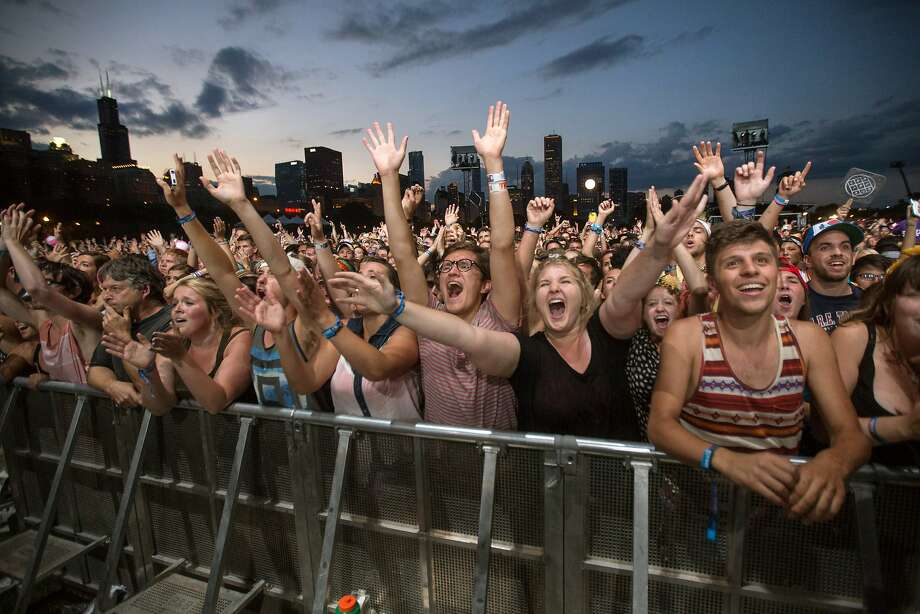 FILE - This Aug. 3, 2013 file photo shows fans reacting while Mumford & Sons performs at the Lollapalooza Festival in Chicago. Lollapalooza marks its 10th anniversary in Chicago when it opens for three days starting Friday, Aug. 1, 2014, with a lineup including Eminem, Outkast and Kings of Leon. Lollapalooza became the basis for the modern festival culture and circuit that has evolved since, including events like Bonnaroo, Coachella and a legion of smaller multi-day parties. (AP Photo/Scott Eisen, File) Photo: Scott Eisen, Associated Press