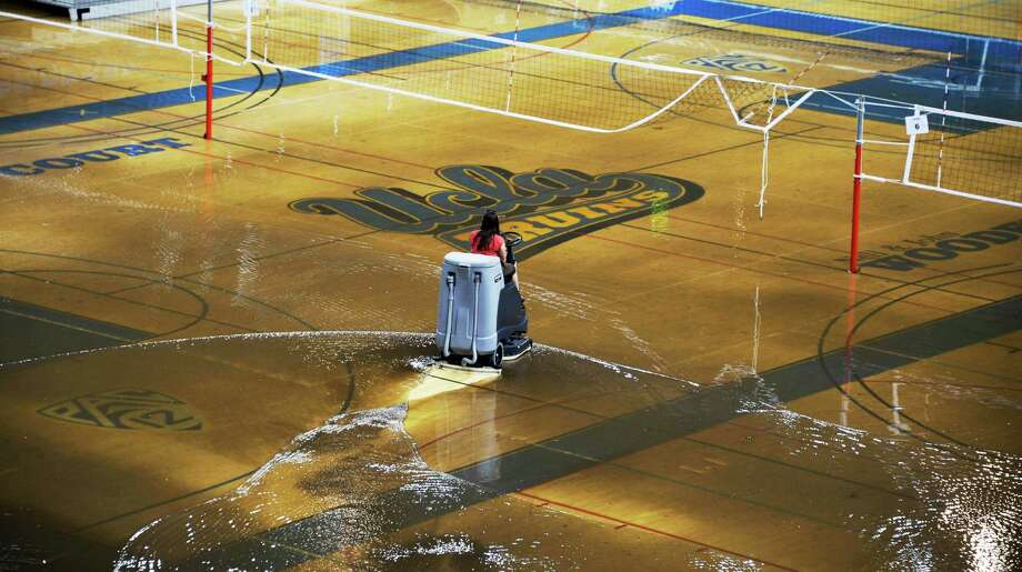 Some of the 10 inches of water that covered the court at UCLA's Pauley Pavilion when a water main broke is removed. Kim Schmaader, in charge of campus facilities said the court is buckling, but the school was still working to save it. Photo: Mike Meadows, FRE / FR55673 Ap