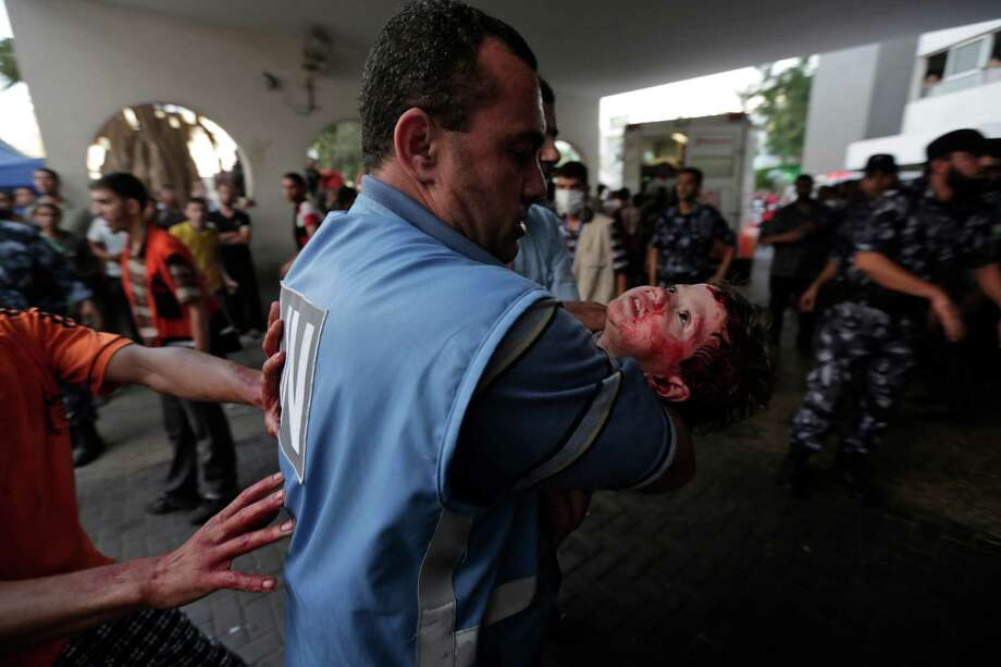 A wounded Palestinian girl is rushed into a Gaza hospital Wednesday on a day that a U.N. school and shopping district were bombed. Story on page A13 Photo: Lefteris Pitarakis, STF / AP