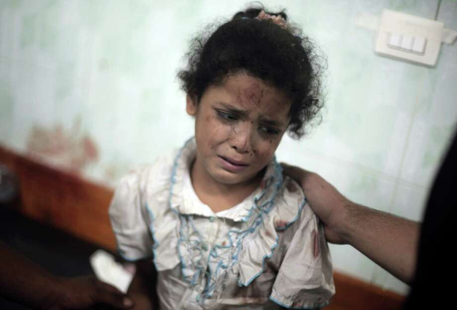 A Palestinian girl cries while receiving treatment for her injuries caused by an Israeli strike at a U.N. school in Jebaliya refugee camp,  at the Kamal Adwan hospital in Beit Lahiya, northern Gaza Strip, Wednesday, July 30, 2014. Several Israeli tank shells slammed into the crowded U.N. school used as shelter for refugees in the Gaza war early on Wednesday, a Palestinian health official and a U.N. official said. (AP Photo/Khalil Hamra) ORG XMIT: KH113 Photo: Khalil Hamra / AP