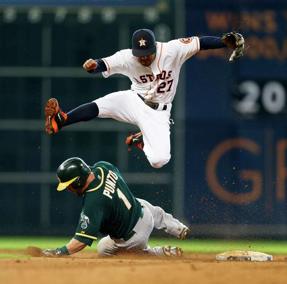 Astros second baseman Jose Altuve takes flight to avoid the Athletics' Nick Punto on a force play in the eighth inning Wednesday. Photo: Karen Warren, Staff / © 2014 Houston Chronicle