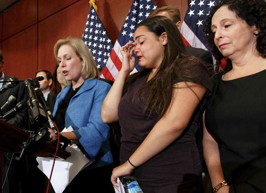 """Anna, center, a survivor of sexual assault, with her mother Susan, right, joins Sen. Kirsten Gillibrand, D-N.Y., left, during a news conference on Capitol Hill in Washington, Wednesday, July 30, 2014, to discuss  """"Campus Accountability and Safety Act"""" that is before the Senate. Anna was an 18 year old student at Hobart and William Smith Colleges in central New York when she was sexually assaulted by fellow students at a fraternity party, just three weeks into her freshman year. (AP Photo/J. Scott Applewhite) ORG XMIT: DCSA106 Photo: J. Scott Applewhite / AP"""