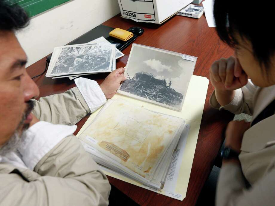 Usan Kurata, left, and Yukari Akatsuka of the nonprofit Kuentai group sort through World World II photos of Saipan, looking for data they hope will lead them to the remains of American MIAs killed during a bloody attack on Saipan. Photo: Mike Groll, STF / AP