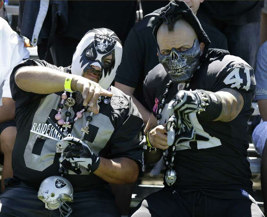 Oakland Raiders fans gesture on the sidelines during their NFL football training camp Saturday, July 26, 2014, in Napa, Calif. (AP Photo/Eric Risberg) Photo: Eric Risberg, Associated Press / AP
